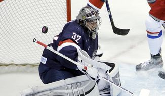 USA goaltender Jonathan Quick deflects a shot against Russia in the first period of a men's ice hockey game at the 2014 Winter Olympics, Saturday, Feb. 15, 2014, in Sochi, Russia. (AP Photo/David J. Phillip )