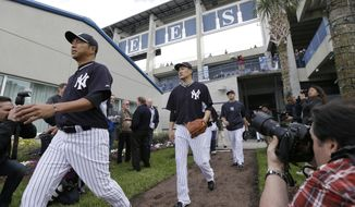 New York Yankees pitchers Masahiro Tanaka, center, and Hiroki Kuroda, left, walk to the field before spring training baseball practice Saturday, Feb. 15, 2014, in Tampa, Fla. (AP Photo/Charlie Neibergall)