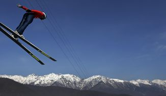 Bryan Fletcher of the United States soars through the air during a Nordic Combined training at the 2014 Winter Olympics, Sunday, Feb. 16, 2014, in Krasnaya Polyana, Russia. (AP Photo/Matthias Schrader)