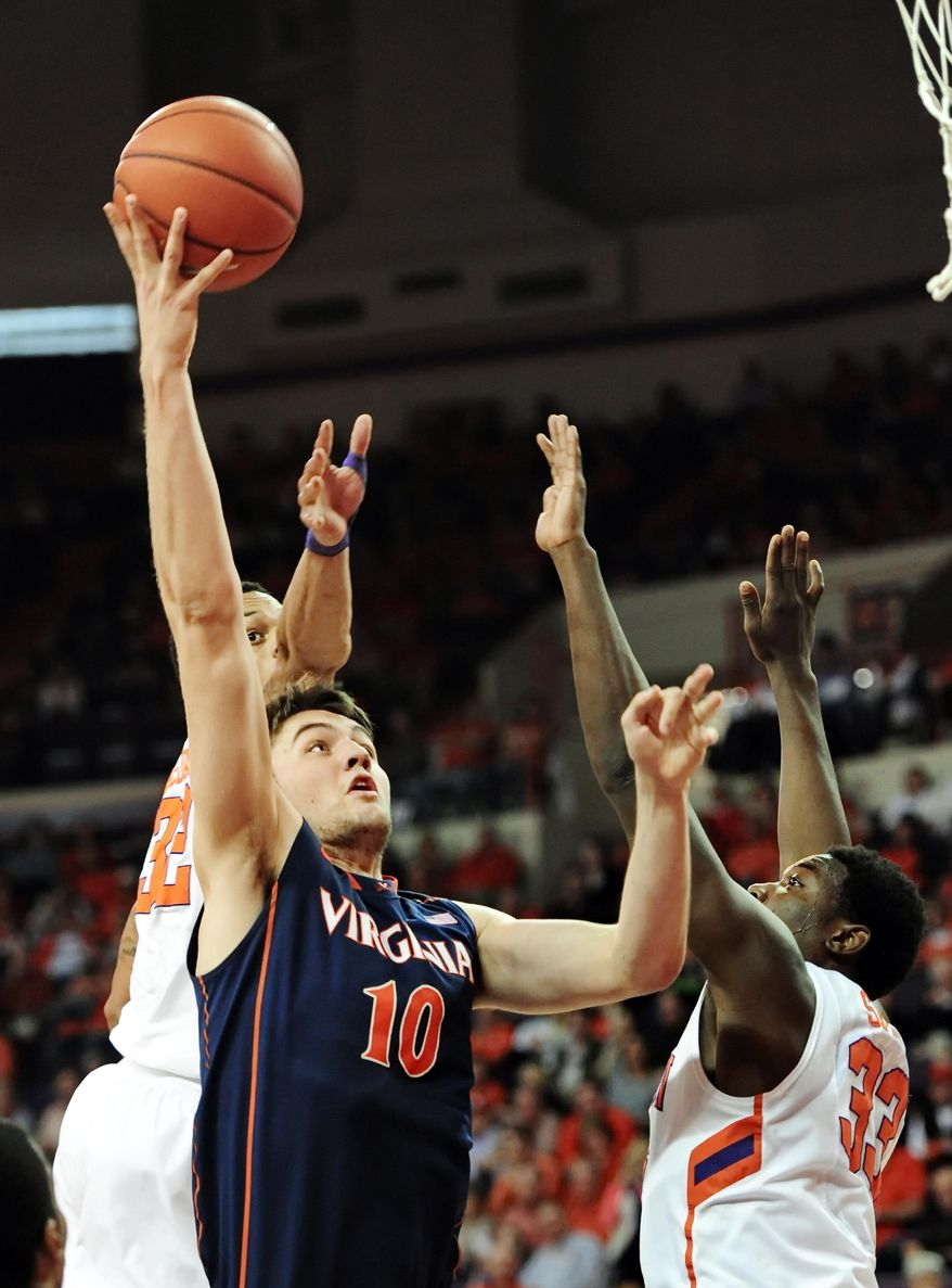 Virginia's Mike Tobey drives to the basket while being covered by Clemson's K.J. McDaniels (32) and Josh Smith during the first half of an NCAA college basketball game Saturday, Feb. 15, 2014, at Littlejohn Coliseum in Clemson, S.C.(AP Photo/ Richard Shiro)
