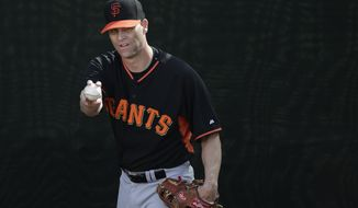 San Francisco Giants pitcher Tim Hudson warms up to throw during spring training baseball practice on Sunday, Feb. 16, 2014, in Scottsdale, Ariz. (AP Photo/Gregory Bull)