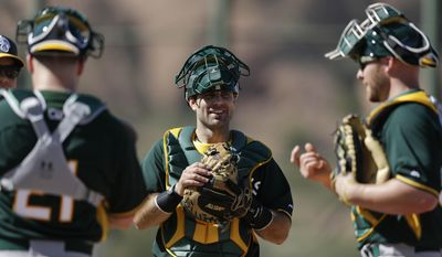 Oakland Athletics invitee catcher Dusty Brown, center, listens to Athletics catchers Stephen Vogt, left, and Chris Gimenez, right, during spring training baseball practice Saturday, Feb. 15, 2014, in Scottsdale, Ariz.  (AP Photo/Gregory Bull)