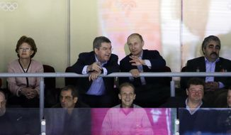 Russian President Vladimir Putin, center right, talks with IOC President Thomas Bach while watching the USA Russia men's hockey game from a box at the 2014 Winter Olympics, Saturday, Feb. 15, 2014, in Sochi, Russia. (AP Photo/David J. Phillip )