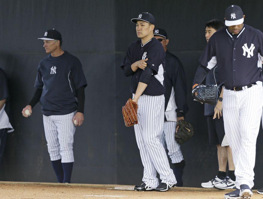 New York Yankees starting pitcher Masahiro Tanaka, center, pitches in the bullpen during spring training baseball practice Saturday, Feb. 15, 2014, in Tampa, Fla. (AP Photo/Charlie Neibergall)