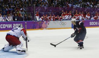 USA forward T.J. Oshie prepares to take a shot against Russia goaltender Sergei Bobrovski in an overtime shootout during a men's ice hockey game at the 2014 Winter Olympics, Saturday, Feb. 15, 2014, in Sochi, Russia. Oshie scored the winning goal and the USA won 3-2. (AP Photo/Julio Cortez)