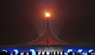 Spectators walk past the Olympic flame on a foggy night in Olympic Park during the 2014 Winter Olympics on Sunday, Feb. 16, 2014, in Sochi, Russia. (AP Photo/J. David Ake)