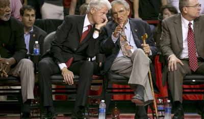 Former president Bill Clinton and former Arkansas coach Eddie Sutton, right, talk during the second half of an NCAA college basketball game between Arkansas and LSU on Saturday, Feb. 15, 2014, in Fayetteville, Ark. (AP Photo/Gareth Patterson)