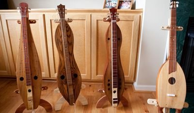 ADVANCE FOR TUESDAY FEB. 18 - This Jan. 2,  2014 photo shows dulcimers made by Frank Brown come in a variety of shapes in Lincolnton, N.C. Lincolnton resident Frank Brown likes knowing he can take a piece of wood that would have otherwise been cut up or used to build a barn, he said, and turn it into an object that produces a beautiful sound. For the last eight years, the 72-year-old has been crafting handmade dulcimers at his home. (AP Photo/Lincoln Times News, Jaclyn Anthony)