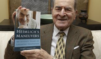 In this Wednesday, Feb. 5, 2014 photo, Dr. Henry Heimlich holds his memoirs prior to being interviewed at his home in Cincinnati. Heimlich is known for developing the Heimlich maneuver that has been used to clear obstructions from the windpipes of choking victims around the world for four decades. (AP Photo/Al Behrman)