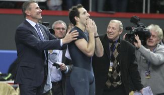 "France's Renaud Lavillenie, center, celebrates after setting a new world indoor record of 6.16 meters while legendary Sergey Bubka, left, congratulates the winner at the ""Pole Vault Stars"" event at Donetsk in eastern Ukraine, Saturday, Feb. 15, 2014. Lavillenie broke Sergei Bubka's 21-year-old indoor pole vault world record. (AP Photo)"