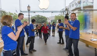 **FILE** Apple sales associates cheer customers as they welcome in the first customs in line for the latest versions of the iPhone, before the opening day of sales of the iPhone 5s and iPhone 5C at the Apple store at the Americana at Brand mall in Glendale, Calif., Friday, Sept. 20, 2013. (AP Photo/Damian Dovarganes)