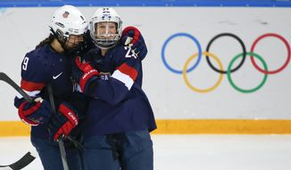 Megan Bozek of the United States, left, congratulates teammate Kacey Bellamy after Bellamy scored a goal against Sweden during the first period of the 2014 Winter Olympics women's semifinal ice hockey game at Shayba Arena Monday, Feb. 17, 2014, in Sochi, Russia. (AP Photo/Julio Cortez)
