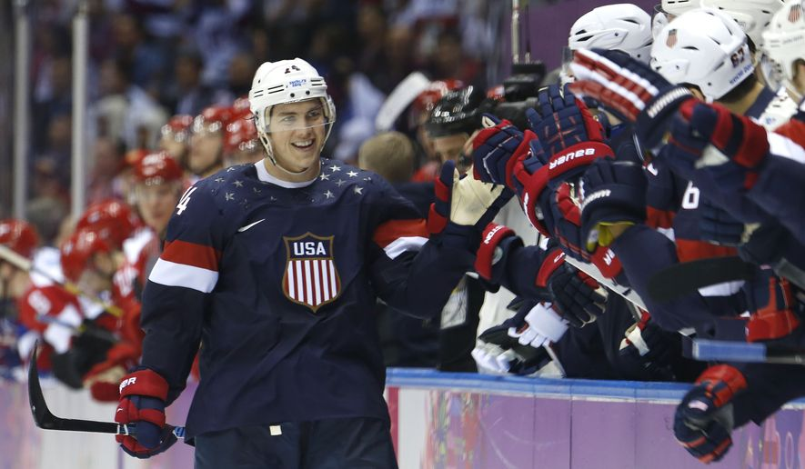 USA forward T.J. Oshie is greeted by treammates after scoring a goal during a shootout against Russia in overtime of a men's ice hockey game at the 2014 Winter Olympics, Saturday, Feb. 15, 2014, in Sochi, Russia. (AP Photo/Mark Humphrey)