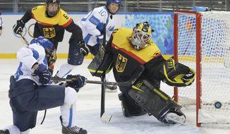 Karolina Rantamaki of Finland shots past Goalkeeper Jennifer Harss of Germany during the 2014 Winter Olympics women's ice hockey game at Shayba Arena, Sunday, Feb. 16, 2014, in Sochi, Russia. (AP Photo/Matt Slocum)