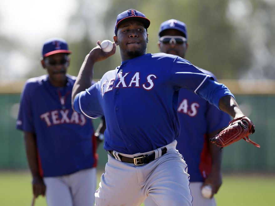 Texas Rangers' Neftali Feliz throws during batting practice as manager Ron Washington, left, and Darren Oliver, right rear, watch during spring training baseball practice, Monday, Feb. 17, 2014, in Surprise, Ariz. (AP Photo/Tony Gutierrez)