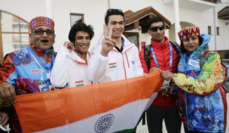 Indian athletes, alpine skier Thakur Himanshu, second left, luger Shiva Keshavan, center, and cross-country skier Nadeem Iqbal, second right, pause for photos after a welcome ceremony for the Indian Olympic team at the Mountain Olympic Village during the 2014 Winter Olympics, Sunday, Feb. 16, 2014, in Krasnaya Polyana, Russia. (AP Photo/Jae C. Hong)