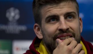 Barcelona's Gerard Pique smiles as he answers questions during a press conference at Manchester City's Etihad Stadium, Manchester, England, Monday Feb. 17, 2014. Barcelona will play Manchester City on Tuesday in a Champions League first knock out round soccer match. (AP Photo/Jon Super)