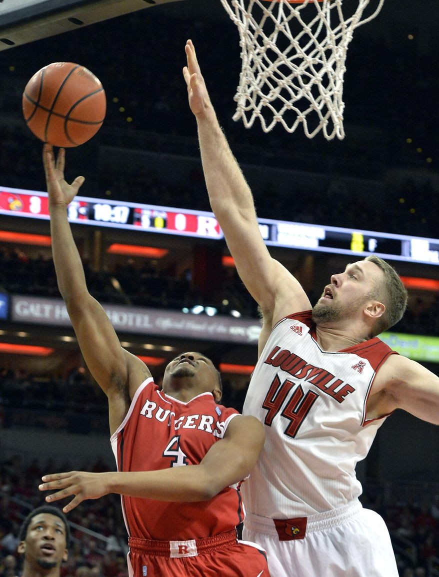 Rutgers Myles Mack, left, attempts a shot over the defense of Louisville's Stephan Van Treese during the first half of an NCAA college basketball game Sunday, Feb. 16, 2014, in Louisville, Ky. (AP Photo/Timothy D. Easley)