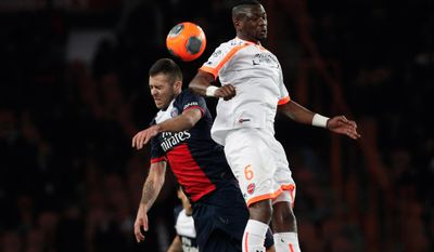 Paris Saint Germain's Jeremy Menez, left, challenges for the ball with Valencienne's Hamed Doumbia, during their French League one soccer match, at the Parc des Princes stadium, in Paris, Friday, Feb. 14, 2014. (AP Photo/Thibault Camus)