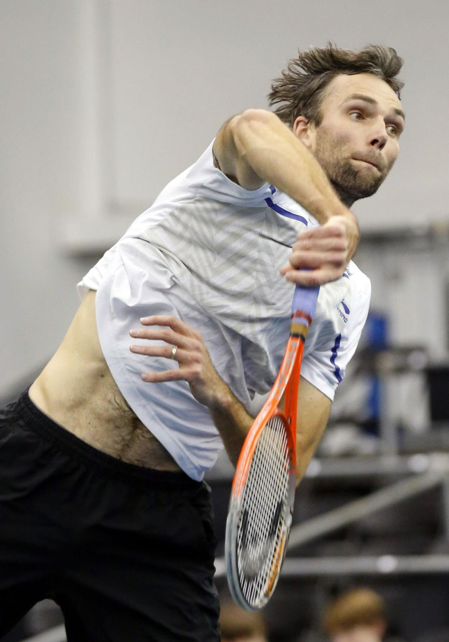 Ivo Karlovic, of Croatia, hits a return to Jack Sock in the quarterfinal match at the U.S. National Indoor Tennis Championships, Friday, Feb. 14, 2014, in Memphis, Tenn. (AP Photo/Rogelio V. Solis)
