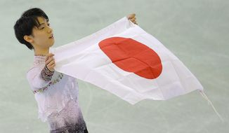 Yuzuru Hanyu of Japan poses with the national flag after he placed first in the men's free skate figure skating final following the flower ceremony at the Iceberg Skating Palace during the 2014 Winter Olympics, Friday, Feb. 14, 2014, in Sochi, Russia. (AP Photo/Vadim Ghirda)