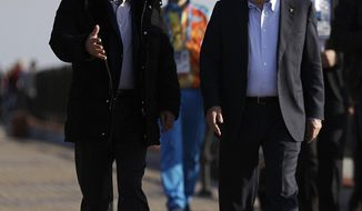 Russian President Vladimir Putin, left, and International Olympic Committee President Thomas Bach walk along the promenade on the Black Sea near the Olympic Park at the 2014 Winter Olympics, Saturday, Feb. 15, 2014, in Sochi, Russia. (AP Photo/David Goldman)