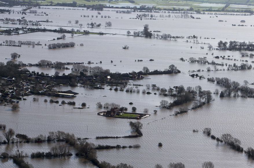 Flood waters inundate the area as one home stands alone and dry near the flooded village of Moorland in Somerset, southwest England, Thursday Feb. 13, 2014.  The house is owned by Sam Notaro, who has built his own levee to hold back the flood waters, as the local communities face further misery in the coming days with heavy rain, wind and snow predicted to sweep across Britain. (AP Photo/Steve Parsons, PA) UNITED KINGDOM OUT - NO SALES - NO ARCHIVES