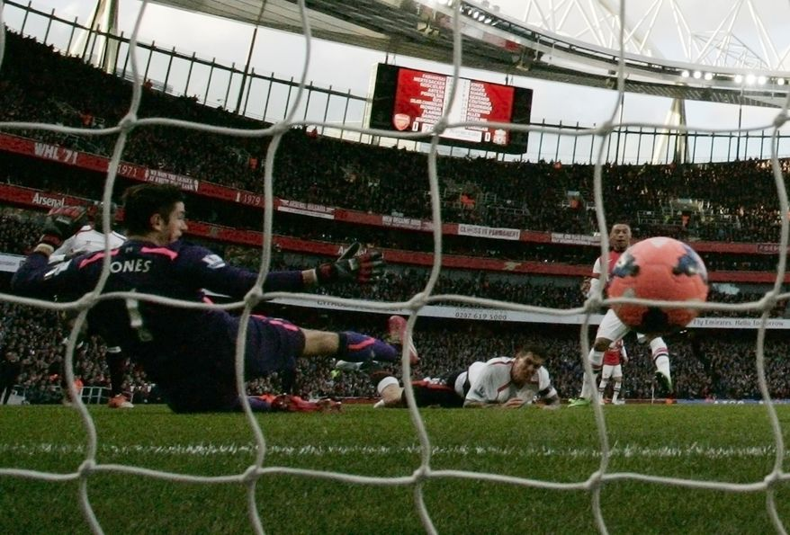 Arsenal's Alex Oxlade-Chamberlain, right, behind ball, scores against Liverpool during their English FA Cup fifth round soccer match at Emirates Stadium in London, Sunday, Feb. 16, 2014. (AP Photo/Sang Tan)