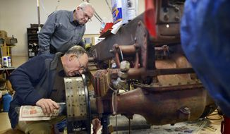 In this Jan. 28, 2014 photo, Dennis Deppert, foreground, and Alan Monts work on the brakes of a 1931 Ahrens Fox fire engine, originally used by the Peoria Fire Dept., that they and other Wheels O' Time Museum volunteers are working to restore in Peoria, Ill. The museum has about 70 volunteers, most retirees. It provides a glimpse of the central Illinois past through a wide variety of objects. (AP Photo/Journal Star, David Zalaznik)