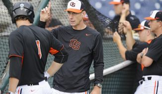 ADVANCE FOR WEEKEND EDITIONS, FEB 15-16- FILE - In this June 14, 2013, file photo, Oregon State coach Pat Casey, center, talks to Tyler Smith (1) during NCAA college baseball practice at TD Ameritrade Park in Omaha, Neb. In what has become something of a mantra for Casey, he opened the season by saying the polls don't matter. One has the perennially ranked Beavers at No. 2, the team's highest ranking ever. (AP Photo/Eric Francis, File)