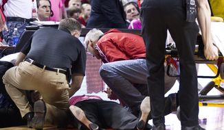 Nebraska head coach Connie Yori is tended to after collapsing on the court during the NCAA women's college basketball game between Nebraska and Indiana at the Pinnacle Bank Arena, Sunday, Feb. 16, 2014, in Lincoln, Neb. She was hospitalized after collapsing. Associate athletic director Marc Boehm said Yori had been bothered by dizzy spells before the end of the game. (AP Photo/The Journal-Star, Morgan Spiehs) LOCAL TV OUT; KOLN-TV OUT; KGIN-TV OUT; KLKN-TV OUT.