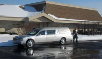 A man walks past a hearse parked outside the Family Center at Wisconsin Memorial Park in Brookfield, Wis., on Friday, Feb. 14, 2014. Wisconsin is one of nine states with laws that prevent cemeteries from owning funeral homes, and funeral directors worry that if the ban is lifted, places like Wisconsin Memorial Park could push them out of business. (AP Photo/Dinesh Ramde)