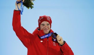 Switzerland's Dario Cologna, the gold medalist in the men's cross-country 15K classical race, smiles while holding his medal during the medals ceremony at the 2014 Winter Olympics, Friday, Feb. 14, 2014, in Sochi, Russia. (AP Photo/David Goldman)