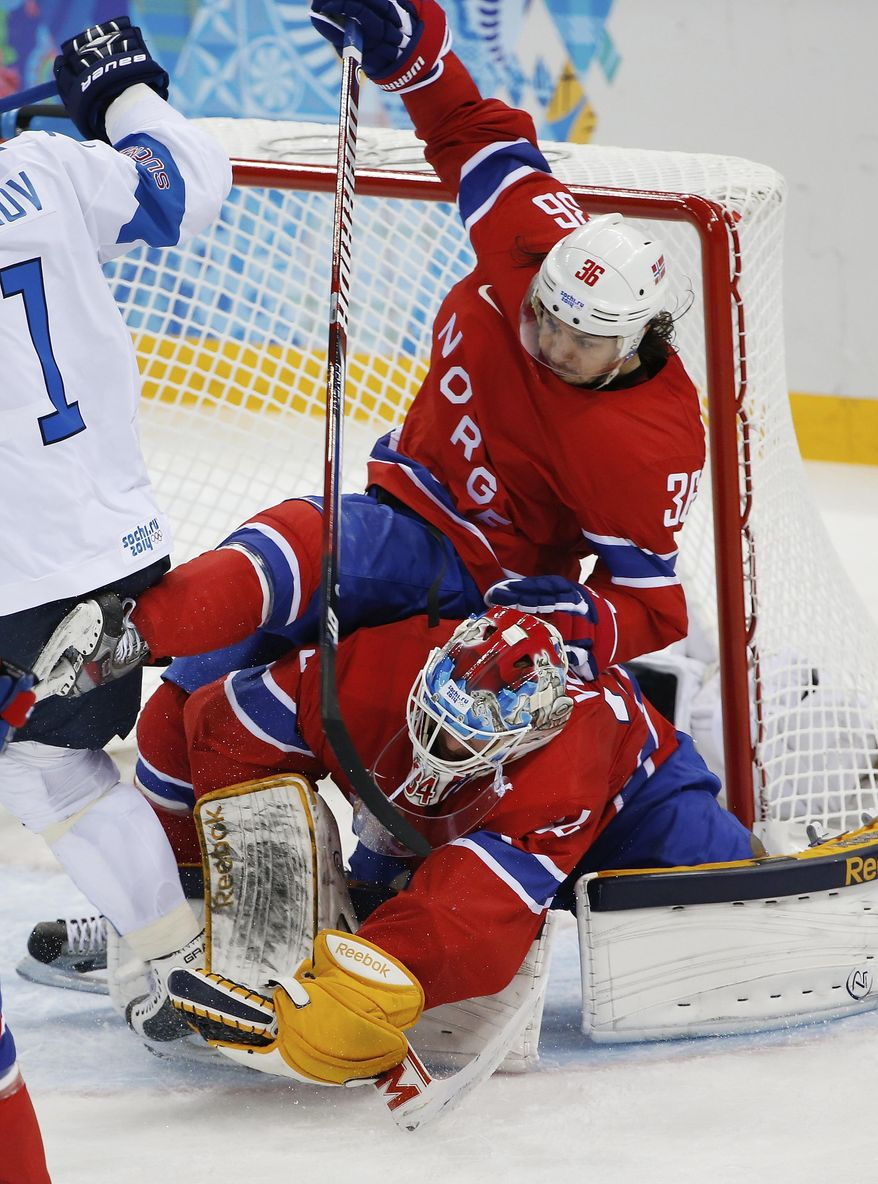 Norway forward Mats Zuccarello lands on goaltender Lars Volden during the 2014 Winter Olympics men's ice hockey game at Shayba Arena, Friday, Feb. 14, 2014, in Sochi, Russia. (AP Photo/Petr David Josek)