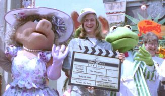 """FILE - Puppeteer John Henson, the son of the late Muppets creator Jim Henson is seen with Muppets Miss Piggy and Kermit at the Disney/MGM studios in Lake Buena Vista, Florida in this June 15, 1990 file photo. Cheryl Henson says her brother died of a """"massive heart attack"""" died at his home in Saugerties, New York on Friday Feb. 14, 2014. He was 48. (AP Photo/FILE)"""