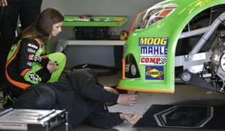Driver Danica Patrick, left, watches as crew members make adjustments to her car during practice for the NASCAR Daytona 500 auto race at Daytona International Speedway in Daytona Beach, Fla., Saturday, Feb. 15, 2014. (AP Photo/John Raoux)