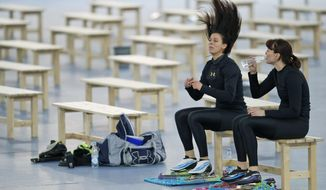 Brittany Bowe of the U.S. unties her hair sitting next Heather Richardson of the U.S., right, after practicing at the Adler Arena Skating Center at the 2014 Winter Olympics, Saturday, Feb. 15, 2014, in Sochi, Russia. (AP Photo/Pavel Golovkin)