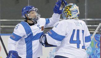 Jenni Hiirikoski of Finland celebrates their 2-1 win over Germany with goalkeeper Noora Raty after the 2014 Winter Olympics women's ice hockey game at Shayba Arena, Sunday, Feb. 16, 2014, in Sochi, Russia. (AP Photo/Matt Slocum)
