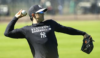 New York Yankees infielder Brian Roberts throws in the outfield during spring training baseball practice, Monday, Feb. 17, 2014, in Tampa, Fla. (AP Photo/Charlie Neibergall)