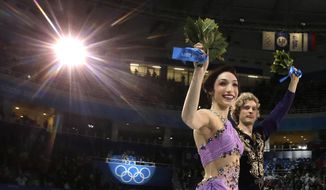 Meryl Davis and Charlie White of the United States celebrate their first place following the flower ceremony in the ice dance free dance figure skating finals at the Iceberg Skating Palace during the 2014 Winter Olympics, Monday, Feb. 17, 2014, in Sochi, Russia. (AP Photo/Darron Cummings)