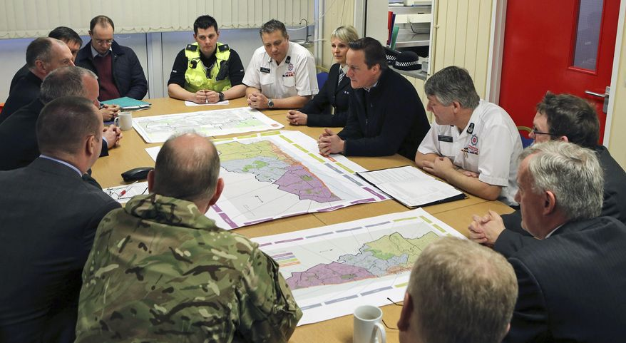 Britain's Prime Minister David Cameron talks to representatives from the emergency services, military, Network Rail and power companies about the recent bad weather in Britain, at Bispham Fire Station, Blackpool, Lancashire, England, Friday, Feb. 14, 2014. (AP Photo/PA, Peter Byrne) UNITED KINGDOM OUT