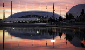 The sun sets as the Bolshoy Ice Dome is reflected in a pool of water underneath the Olympic cauldron at the 2014 Winter Olympics, Thursday, Feb. 13, 2014, in Sochi, Russia. (AP Photo/David Goldman)