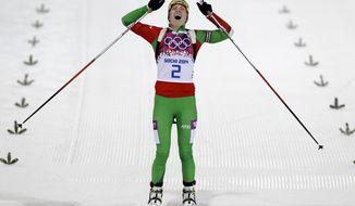 Belarus' Darya Domracheva celebrates winning the gold medal in the women's biathlon 12.5k mass-start, at the 2014 Winter Olympics, Monday, Feb. 17, 2014, in Krasnaya Polyana, Russia. (AP Photo/Kirsty Wigglesworth)