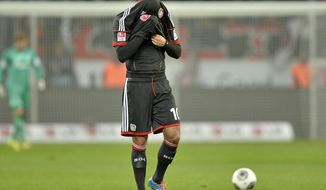 Leverkusen's Emre Can hides under his shirt after his team lost the German Bundesliga soccer match between Bayer Leverkusen and FC Schalke 04 in Leverkusen,  Germany, Saturday, Feb. 15, 2014. Leverkusen was defeated by Schalke 2-1. (AP Photo/Martin Meissner)
