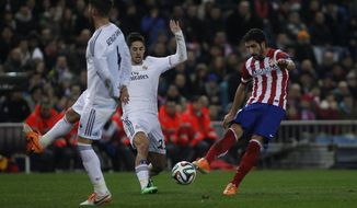 Atletico's Raul Garcia in action with Real's Isco during a semi final, 2nd leg, Copa del Rey soccer derby match between Real Madrid and Atletico Madrid at the Vicente Calderon Stadium in Madrid, Tuesday Feb. 11 , 2014.  (AP Photo/Gabriel Pecot)