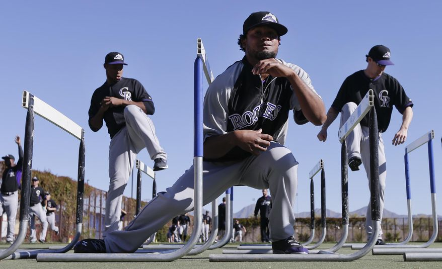 Colorado Rockies pitcher Manuel Corpas, center, ducks under a hurdle in front of teammates LaTroy Hawkins, left, and Greg Burke, right, during spring training baseball practice, Monday, Feb. 17, 2014, in Scottsdale, Ariz.  (AP Photo/Gregory Bull)