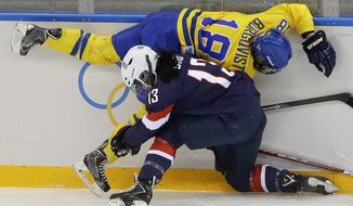 Julie Chu of the United States collides with Anna Borgqvist of Sweden during the first period of the 2014 Winter Olympics women's semifinal ice hockey game at Shayba Arena Monday, Feb. 17, 2014, in Sochi, Russia. (AP Photo/Matt Slocum)