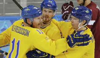 Sweden forward Daniel Alfredsson. left, celebrates his goal against Latvia teammates Daniel Sedin, center, and Nicklas Backstrom, right, during the 2014 Winter Olympics men's ice hockey game at Shayba Arena Saturday, Feb. 15, 2014, in Sochi, Russia. (AP Photo/Matt Slocum)