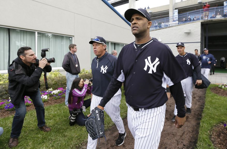 New York Yankees starting pitcher CC Sabathia, right, walks to the field before a spring training baseball practice Saturday, Feb. 15, 2014, in Tampa, Fla. (AP Photo/Charlie Neibergall)