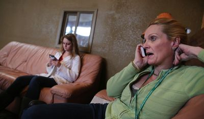 Marijuana store owner Toni Fox, right, speaks on the phone with a reporter, as Fox's daughter and employee Cheyenne sits texting at left, in the lobby of Fox's 3D Cannabis Center, in Denver, Friday Feb. 14, 2014. Fox and others in the marijuana industry breathed a sigh of relief Friday after federal banking regulators issued long-awaited permission for them to access basic banking services. (AP Photo/Brennan Linsley)